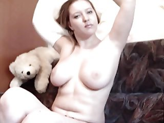 Chubby redhead plays solo on the couch