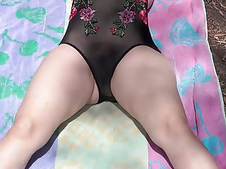 At a park on her back a very transparent one piece swimsuit