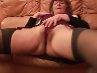 Hairy granny in business suit and stockings showing pussy