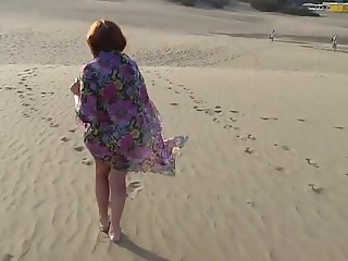 Mature woman posing on the beach and the dunes