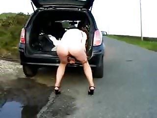 Wife pees by the car