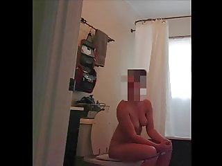 Unaware wife, naked on the toilet