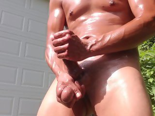 Tan sexy guy oiled up in the front yard