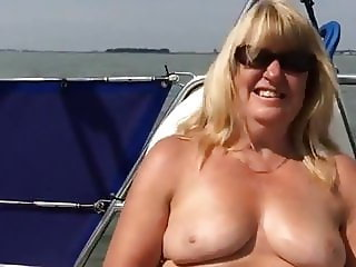 Big titted mature masturbating on a boat.