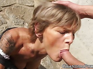 Granny with a perfect body sucking cock outdoors