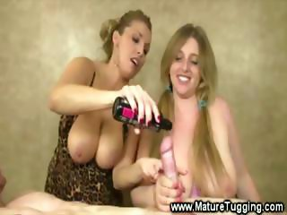 Two blondes share a cock between them as they jerk it off
