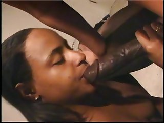 Two black whores suck on one black cock