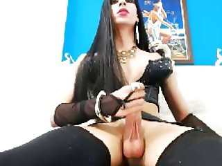 Raven-haired latin shemale with big balls jerks her cock off