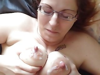 Blue eyed redhead in glasses gets her huge nipples cummed on