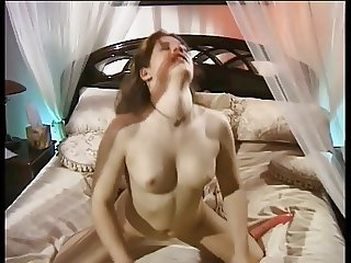 Sexy girl with long hair and small tits finger fucks her pussy on the bed