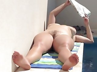 Nude mature wife by the pool