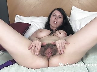 Emily Winters enjoys her hairy pussy while in bed