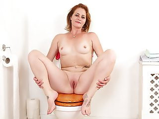British milf Sexy Jozie strips and plays on toilet