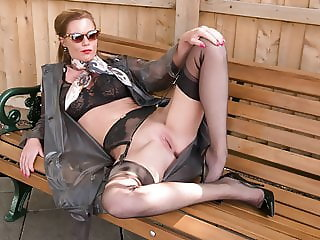 Kinky Milf wanks openly on bench in  nylons garters heels